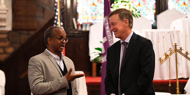 Former Colorado Gov. John Hickenlooper discusses gun control and death penalty issues with Anthony Thompson on Saturday, April 6, 2019, in Charleston, S.C. Thompson's wife was slain in a massacre that claimed nine Bible study participants at a historic black church in South Carolina. Hickenlooper, a staunch advocate for gun control legislation, visited Mother Emanuel during a campaign trip to the state as he seems the Democratic presidential nomination. (AP Photo/Meg Kinnard)