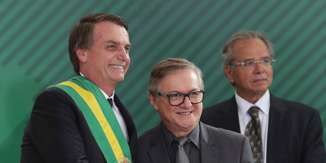 """In this Jan. 1, 2019 photo, Brazil's President Jair Bolsonaro, left, shakes hands with Education Minister Ricardo Velez Rodriguez, during a swearing-in ceremony for his cabinet at the Planalto presidential palace, in Brasilia, Brazil. Velez Rodriguez said on Wednesday, April 3, 2019, that he will have school books revised to refer to the 1964 military coup as a """"democratic regime by force."""" (AP Photo/Eraldo Peres)"""