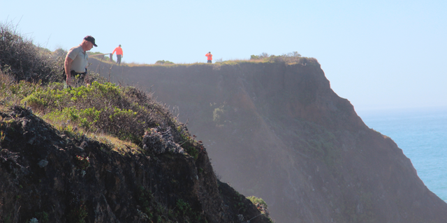 FILE - In this March 29, 2018 file photo, Deputy Bill Holcomb looks down the cliff near the crash site near Mendocino, Calif., as search and rescue volunteers scour the area behind him on and resume looking for children, still missing after their parent's SUV plunged into the ocean Monday. A California Highway Patrol investigator testified Thursday, April 4, 2019 that Sarah Hart searched whether death by drowning was relatively painless hours before her wife drove an SUV off a cliff, killing them and six adopted children in waters below. A special coroner's jury in Mendocino County is trying to determine whether the March 2018 deaths were murder-suicide or accidental. (Kale Williams/The Oregonian via AP)