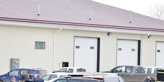 Law enforcement officers stand outside RJR Maintenance and Management in Mandan, North Dakota on Monday.