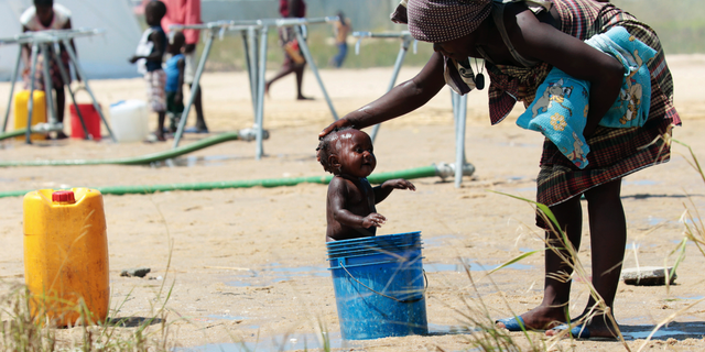 A mother bathing her baby in a bucket at a camp for displaced survivors of Cyclone Idai in Beira, Mozambique, last month. (AP Photo/Tsvangirayi Mukwazhi, File)