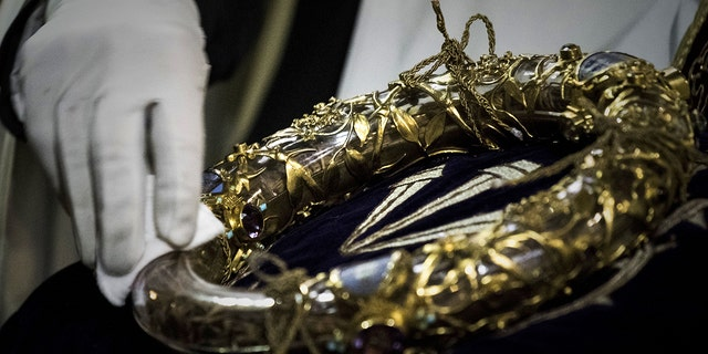 A priest wipes the Crown of Thorns, a relic of the passion of Christ- at the Notre-Dame Cathedral in Paris on April 14, 2017. (PHILIPPE LOPEZ/AFP/Getty Images)