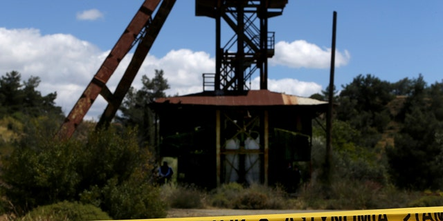 Cypriot investigators and police search a flooded mineshaft where two female bodies were found, outside Mister village near the capital Nicosia, Cyprus, Monday, April 22, 2019.