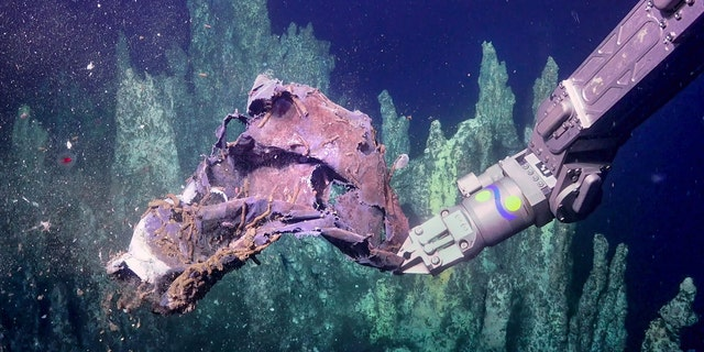 ROV SuBastian picks up some discarded trash near Big Pagoda vent in the Guaymas Basin. (Courtesy of Schmidt Ocean Institute)