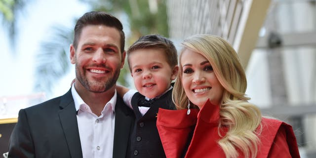 Carrie Underwood is pictured here with husband Mike Fisher and their son Isaiah at Underwood's star unveiling ceremony on the Hollywood Walk of Fame on September 20, 2018. On Sunday, the proud parents revealed how their 4-year-old son ended his Easter.