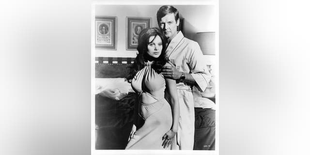 """Madeline Smith leaning against Roger Moore in a suggestive manner as he touches her arm in a scene from the film """"Live And Let Die,"""" circa 1973."""