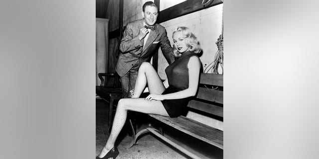 American actress and pin-up model Joi Lansing (1928 - 1972) with an admirer, circa 1955. She is wearing shorts and fishnet stockings.