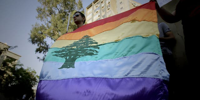 A gay pride flag bearing the cedar tree in the middle of it is carried by human rights activists during an anti-homophobia rally in Beirut on April 30, 2013. Top Lebanese military prosecutors acquitted four military personnel Saturday in a landmark ruling that affirms homosexuality is not a crime.