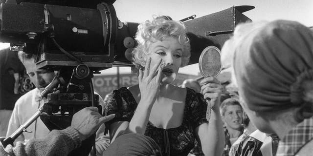 """1956: American actress Marilyn Monroe (1926 - 1962) adjusts her make-up, using a handheld mirror on the set of director Joshua Logan's film, """"Bus Stop."""" She is standing next to a movie camera in a crowd of people. —Photo by Hulton Archive/Getty Images"""