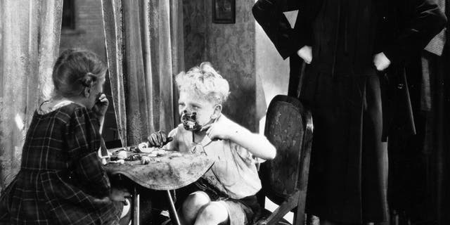 """1926: Silent film star Colleen Moore (1900 - 1988) despairs at the table manners of two mucky children in a scene from the film """"Irene,"""" directed by Alfred E Green for First National. The girl is child actress Fay McKenzie and the boy is Bobby Lloyd. —Photo by Hulton Archive/Getty Images"""