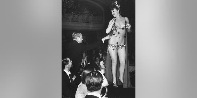 Famous burlesque star stripper Gypsy Rose Lee getting a $10 star plucked from her nude netting by wealthy mogul William Rhinelander Stewart during her show to raise money for the British War Relief Society, at the Astor Hotel.