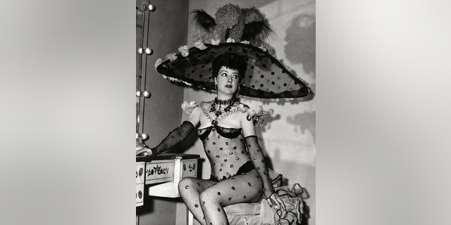 Gypsy Rose Lee wearing a one-piece fishnet unitard with large sequins, matching gloves and a large feather and netting hat.