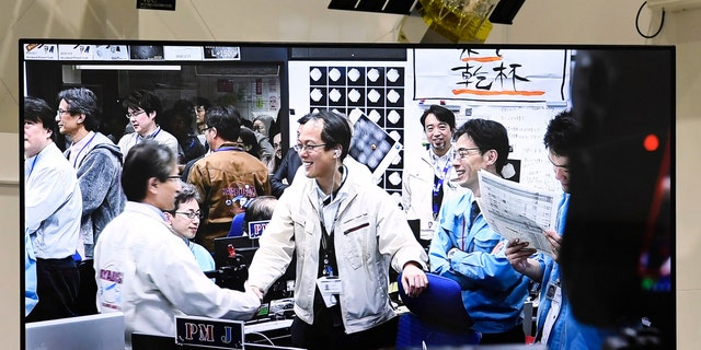 Members of The Japan Aerospace Exploration Agency, or JAXA, seen on screen, celebrate, as Hayabusa2 spacecraft safely evacuated and remained intact after the blast, in Sagamihara, near Tokyo, Friday, April 5, 2019.