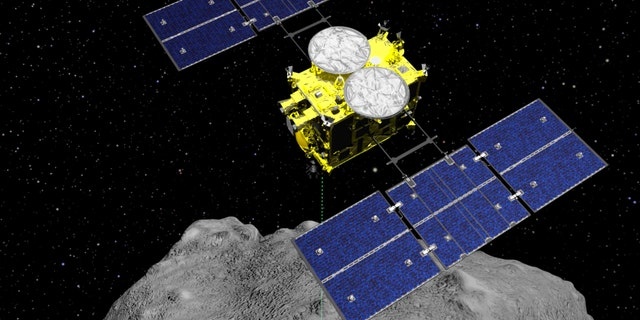 In this computer graphics image released by the Japan Aerospace Exploration Agency (JAXA), the Hayabusa2 spacecraft is seen above the asteroid Ryugu.