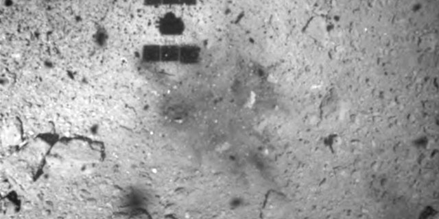 FILE - This Feb. 22, 2019, file image released by the Japan Aerospace Exploration Agency (JAXA) shows the shadow, center above, of the Hayabusa2 spacecraft after its successful touchdown on the asteroid Ryugu.