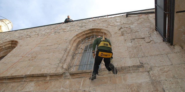 Abseiling a walls of a Last Supper room.