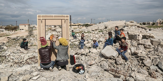 Puppeteer Walid Rashed performs a puppet act for Syrian children, in the midst of the rubble of damaged buildings, to mark the World Theatre Day as part of his tour of Saraqib in the rebel-held province of Idlib.