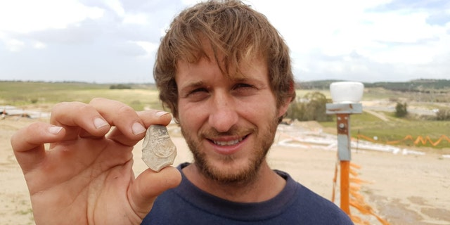 IAA Archaeologist Avinoam Lehavi holding the ancient oil lamp sherd decorated with a menorah. (Anat Rasiuk, Israel Antiquities Authority)