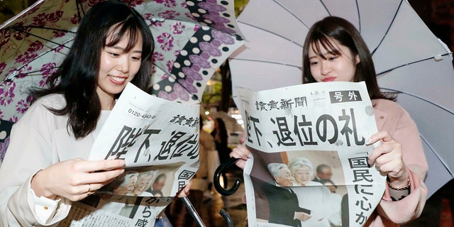 "Women read a copy of the extra edition of Yomiuri Shimbun newspaper reporting Emperor Akihito's abdication in Tokyo Tuesday. The headline reads ""Emperor, abdication ritual."" (Kyodo News via AP)"