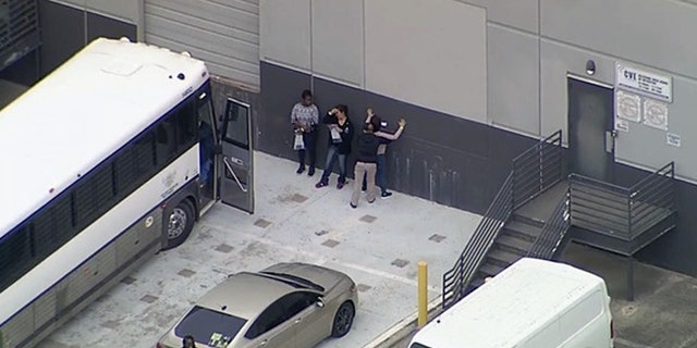 Workers are searched outside CVE Group in Allen, Texas, on Wednesday.