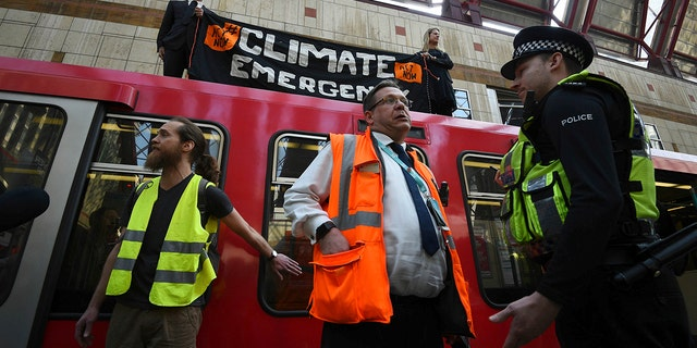 Police and officials stand by as climate activists protest atop a Dockland Light Railway carriage at Canary Wharf station in London, as part of the ongoing climate change demonstrations in the capital, Wednesday April 17, 2019. The environment protest group Extinction Rebellion are calling for general public protests with civic disobedience held over several days, to highlight what it says is the failure to tackle the causes of climate change.