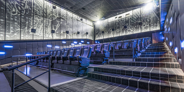 Pictured is a theater equipped with MX4D full motion cinema chairs that spray water, drop snow from the ceiling and whip the viewer around as if they were in the film.