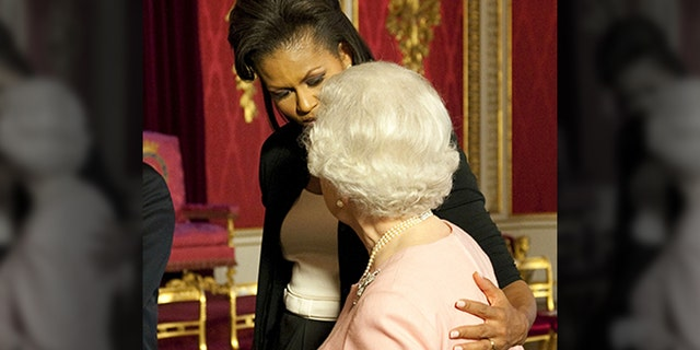 FILE: Former first lady Michelle Obama walks with Queen Elizabeth II at a reception at Buckingham Palace in London on Wednesday, April 1, 2009.