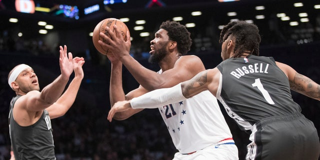 Philadelphia 76ers center Joel Embiid (21) goes to the basket against Brooklyn Nets guard D'Angelo Russell (1)and forward Jared Dudley during the first half of Game 4 of a first-round NBA basketball playoff series, Saturday, April 20, 2019, in New York. (AP Photo/Mary Altaffer)