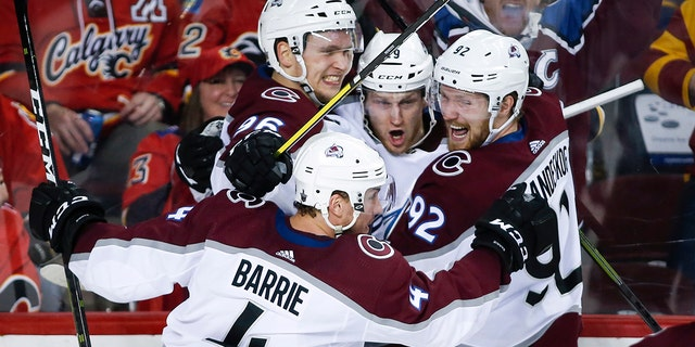 Colorado Avalanche center Nathan MacKinnon (29) celebrates his game-winning goal with teammates Tyson Barrie (4), Mikko Rantanen (96) and Gabriel Landeskog (92) during overtime of an NHL hockey playoff game against the Calgary Flames, in Calgary, Alberta, Saturday, April 13, 2019. (Jeff McIntosh/The Canadian Press via AP)