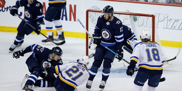 St. Louis Blues center Tyler Bozak (21) scores on Winnipeg Jets goaltender Connor Hellebuyck (37) as Jets defenseman Tyler Myers (57) and Jets right wing Kevin Hayes (12) defend during the third period of Game 1 of an NHL hockey first-round playoff series Wednesday, April 10, 2019, in Winnipeg, Manitoba. (John Woods/The Canadian Press via AP)