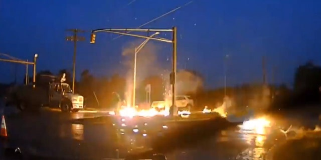 Flames can be seen after a powerline fell to the wet ground and exploded into a fireball as a utility worker was nearby in New Jersey on Monday.