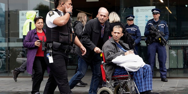 A man in a wheelchair is escorted from outside the High Court in Christchurch, New Zealand, on Friday. (Associated Press)
