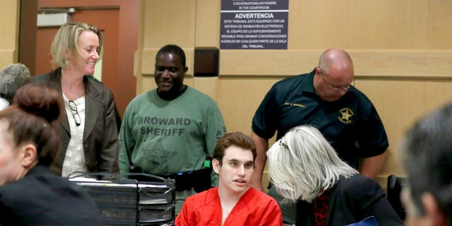 Parkland school shooting suspect Nikolas Cruz speaks with his attorney in court for a defense motion at the Broward Courthouse in Fort Lauderdale, Fla., Thursday, April 18, 2019.