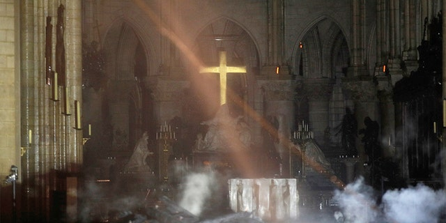 Smoke is seen around the alter inside Notre Dame cathedral in Paris, Monday, April 15, 2019. The golden altar cross could be seen glowing as firefighters made their way in.