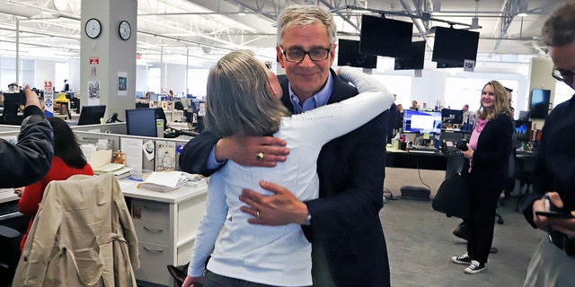 Pittsburgh Post Gazette retired Executive Editor David Shribman, center right, hugs city editor Lillian Thomas after the paper was awarded the Pulitzer Prize for Breaking News Reporting. (AP Photo/Gene J. Puskar)