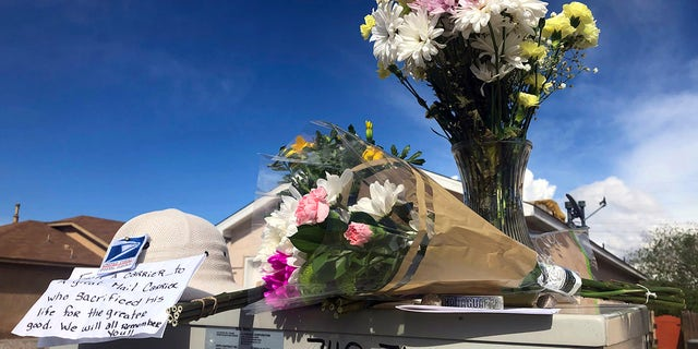 Flowers and notes are arranged atop a mailbox on April 23, 2019, in tribute to a mail carrier who police say was killed outside an adjacent home in Albuquerque, N.M. (Associated Press)