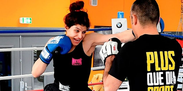 Iranian boxer Sadaf Khadem (L) trains with French Iranian former world boxing champion Mahyar Monshipour in a gymnasium in Royan, southwestern France, on April 11, 2019 ahead of her first fight.