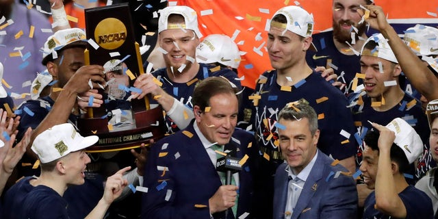 Virginia head coach Tony Bennett, right, celebrates with his team after the championship game against Texas Tech in the Final Four NCAA college basketball tournament, Monday, April 8, 2019, in Minneapolis. Virginia won 85-77 in overtime.(AP Photo/Matt York)