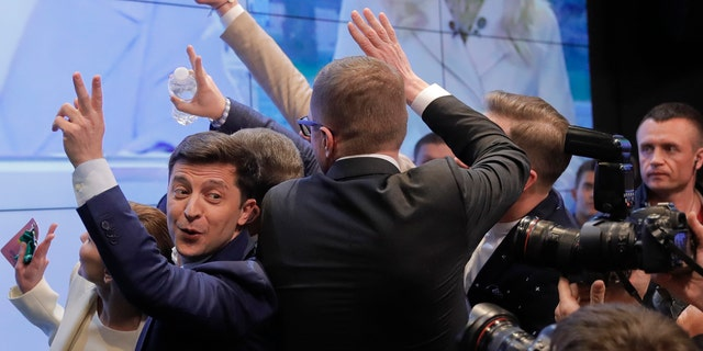 In this Sunday, April 21, 2019, photo, Ukrainian comedian and presidential candidate Volodymyr Zelenskiy, left, makes the victory sign after seeing the exit polls for the second round of presidential elections in Kiev, Ukraine.