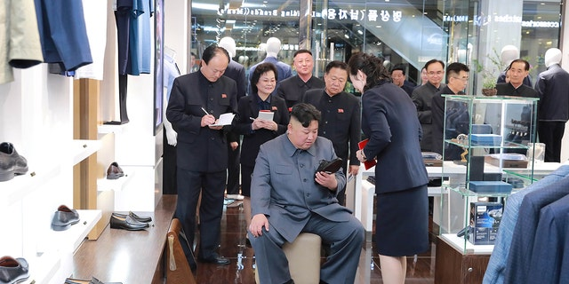 Kim Jong Un inspecting a shoe during his visit to Taesong Department Store in Pyongyang.