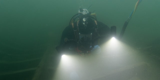 A diver examines the wreck.
