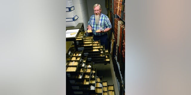 Historian Randy Marcum and the unclaimed medals at the West Virginia State Archives.