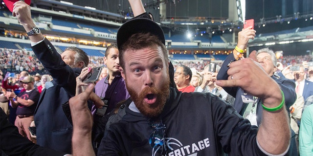 A man gestures towards the press corps after throwing an object on stage towards US President Donald Trump as he is speaking at the National Rifle Association (NRA) Annual Meeting at Lucas Oil Stadium in Indianapolis, Indiana, April 26, 2019. - The man was later removed from the scene by Secret service agents. (Photo by SAUL LOEB / AFP) (Photo credit should read SAUL LOEB/AFP/Getty Images)