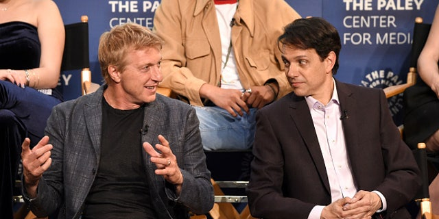 """William Zabka, left, and Ralph Macchio speak onstage at the """"Cobra Kai"""" premiere at The Paley Center for Media on April 22 in Beverly Hills, California."""
