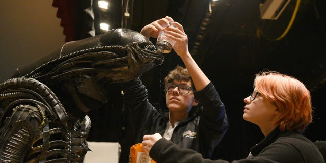 """North Bergen High School's Xavier Perez, 16, the Alien, is covered in slime by his handlers Eddie Mantilla, 15, and Cassandra Klima, 16, as they work on the play """"Alien,"""" an adaptation of the Ridley Scott movie, in North Bergen, N.J."""