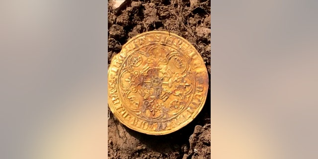 One of the gold coins. The four hunters struck gold in a field in Buckinghamshire and were initially delighted to find 12 ornately decorated silver Edward I and II coins. Over four days they excavated 557 coins - including 12 ultra-rare full gold nobles from the time of the Black Death. (Credit: SWNS)