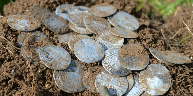 Some of the silver coins. The men - more used to digging up shotgun shells and thimbles than treasure - were astonished to find coin after coin from the hidden ancient hoard. (Credit: SWNS)