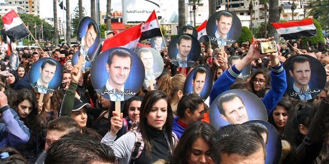 In this photo released by the Syrian official news agency SANA, people hold Syrian flags and portraits of President Bashar Assad during a protest against U.S. President Donald Trump's move to recognize Israeli sovereignty over the Israeli occupied Golan Heights, in the coastal port city of Tartus, Syria, Wednesday, March. 27, 2019.