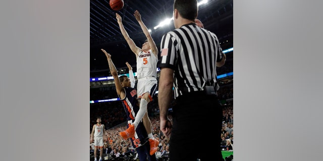 Virginia's Kyle Guy (5) takes a shot as Auburn's Samir Doughty (10) was called for a foul with 0.6 seconds left in the semi-final. (AP Photo/David J. Phillip)