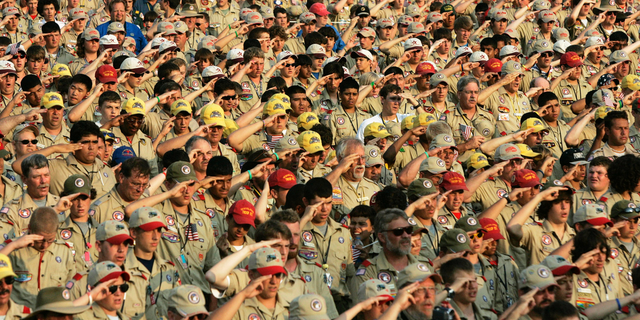 FILE - In this July 31, 2005 file photo, Boy Scouts salute as they recite the Pledge of Allegiance during the Boy Scout Jamboree in Bowling Green, Va. In 2019, financial threats to the Boy Scouts have intensified as multiple states consider adjusting their statute-of-limitations laws so that victims of long-ago child sex-abuse have a chance to seek redress in the courts. (AP Photo/ Haraz N. Ghanbari)